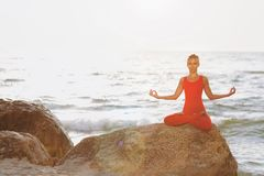 A woman in a red suit practicing yoga on stone at sunrise near the sea. The woman in a red suit practicing yoga on stone at sunrise near the sea Stock Photos