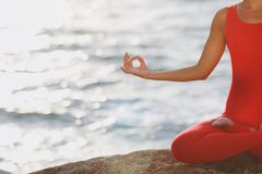 A woman in a red suit practicing yoga on stone at sunrise near the sea. The woman in a red suit practicing yoga on stone at sunrise near the sea Stock Images
