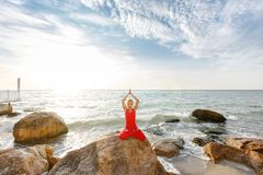 A woman in a red suit practicing yoga on stone at sunrise near the sea. The woman in a red suit practicing yoga on stone at sunrise near the sea Stock Image
