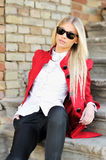 Woman in red suit and sunglasses. Young woman in red suit and sunglasses outdoor portrait stock image