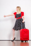 Woman with red suitcase hitchhiking. Traveling vacation ew life concept. Elegant lovely woman wearing polka dot black dress with red suitcase ready for trip Royalty Free Stock Photo