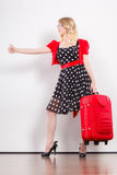 Woman with red suitcase hitchhiking. Traveling vacation ew life concept. Elegant lovely woman wearing polka dot black dress with red suitcase ready for trip Stock Photography