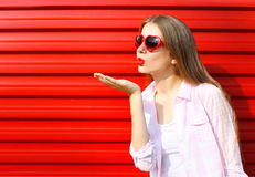 Woman in red sunglasses sends an air kiss over colorful Royalty Free Stock Image