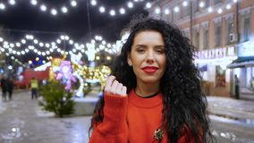 Woman in a red sweater. Beautiful dark-haired curly woman in a red sweater looks into the frame while walking along a nightly winter street. A girl with a stock video footage