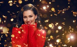 Woman in red sweater on black background stock photos