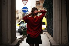 Woman in Red Sweater and Black Miniskirt Holding Hair Facing Road stock photos