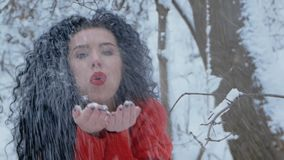 Woman in a red sweater blowing snow. Close-up of a curly brunette woman in a red sweater blowing snow from the palms. Fashionable sexy girl with beautiful smile stock video footage