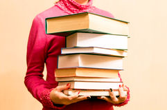 Woman in red sweater with books in hand Stock Images