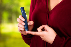 Woman with red sweater checking blood sugar level by glucometer and test stripe at home.  Royalty Free Stock Images