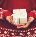 Woman in red sweater holding christmas giftbox with red and whit Royalty Free Stock Photo