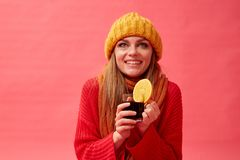Girl in a red sweater and knitted hat holding a cup of hot mulled wine with an orange slice. Red background. Studio. Woman in a red sweater and knitted hat royalty free stock image