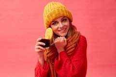 Girl in a red sweater and knitted hat holding a cup of hot mulled wine with an orange slice. Red background. Studio. Woman in a red sweater and knitted hat stock photo