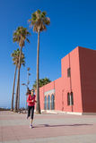 Woman running in promenade of Benalmadena. Woman with red sweater running next to Bil Bil Tower, in the promenade of Benalmadena, Malaga, Andalusia, Spain stock photos