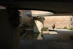 Quiet courtyard at Venice Biennale. A woman in red sweater seating on a bench and reading in a quiet sunny courtyard at Biennale exhibition in Venice stock photo
