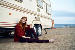 Woman in a red sweater sits on a sandy beach near a trailer, sea, summer royalty free stock photo