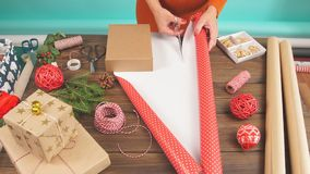 Woman wrapping gift box with decorating items on wood table, close up, top view. stock video footage