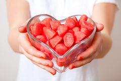 Woman with red sweets. Woman offering red sweets from a heart shaped bowl. Studio shot royalty free stock photography