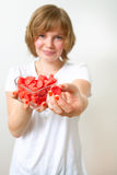 Woman with red sweets. Woman offering red sweets from a heart shaped bowl. Studio shot royalty free stock photo