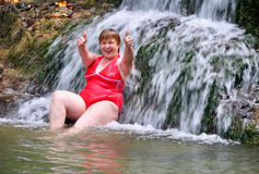 Woman in red swimsuit enjoying a waterfall Stock Image