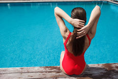Woman in red swimsuit sitting near the pool, summer tan. Royalty Free Stock Photography