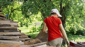 A woman in a red T-shirt in the garden neatly stores firewood from a transport trolley. Logging for winter heating and a. Fireplace stock video