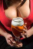 Woman in red t-shirt holding glass of beer. Woman with bust in red t-shirt holding glass of beer stock photos