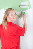 Woman in red t-shirt with paint roller in hand Stock Photo