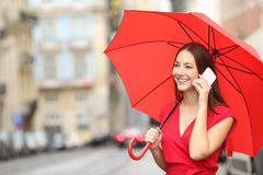 Woman in red talking on a smart phone. Happy woman in red talking on a smart phone under an umbrella in the street of an old town Stock Images