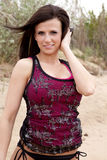 Woman red tank top hand in hair. A woman in a red tank top in the sand Royalty Free Stock Images
