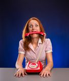 Woman with red telephone in her mouth Stock Photography