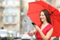 Woman in red texting on a smart phone Royalty Free Stock Images