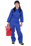 Woman with red toolbox. Woman in blue overalls with holding a red toolbox Royalty Free Stock Photo