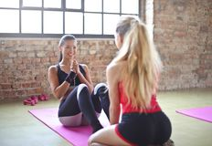 Woman With Red Top And Black Shorts On Purple Yoga Mat Stock Image