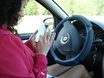 A woman in red top clothes is driving a car using a smartphone. Royalty Free Stock Image