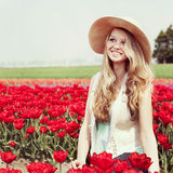 Woman in a red tulip field Stock Images