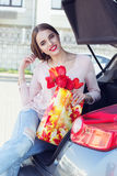 Woman with red tulips sitting in car trunk Royalty Free Stock Photos