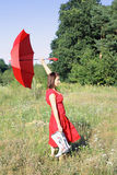 Woman with red umbrella. Woman walking through the meadow with red umbrella Stock Photos