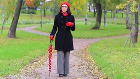 Woman with red umbrella in the autumn park. Elegant woman with glasses and a red umbrella dancing in the autumn park stock video footage