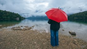 Woman with red umbrella contemplates on rain. In front of a lake. Sad and lonely female person looking into distance Stock Image