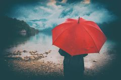 Woman with red umbrella contemplates on rain. In front of a lake. Sad and lonely female person looking into distance. Grunge editing with dirt, noise, splotches Royalty Free Stock Image