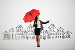 Woman with red umbrella held out her hand. Businesswoman with red umbrella held out her hand and looking up over grey background with drawing street Royalty Free Stock Photos