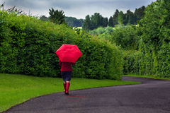 Woman with red umbrella on an overcast day. Photo of a woman walking down a road holding a red umbrella after a heavy downpour of rain on an overcast day royalty free stock image