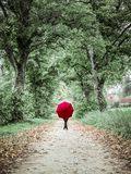 Woman with red umbrella posing in the autumn landscape royalty free stock photography