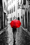 Woman with red umbrella on retro street in the old town. Wind and rain Stock Photography