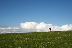 Woman with a red umbrella. Woman standing on top of a hill with a red umbrella Royalty Free Stock Images