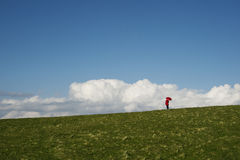 Woman with a red umbrella. Woman standing on top of a hill with a red umbrella Royalty Free Stock Photography