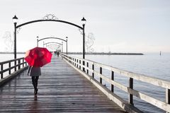 Woman with red umbrella walking on a pier. Stock Photos