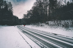 Woman with red umbrella on winter road. Woman holding red umbrella standing on snow covered road through forest in winter Stock Images