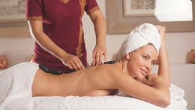 Woman in red uniform doing a massage for awesome girl stock footage