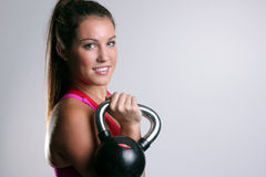 Woman with a red vest holding a kettlebell in the rack position Stock Photography